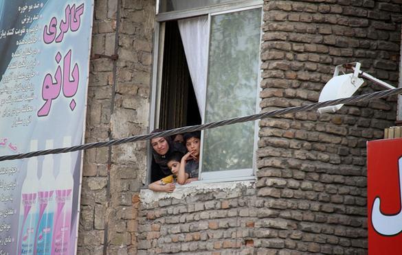 دو کودک همراه با یک زن در حال تماشای اجرای حکم اعدام ۳ مرد از پنجره منزلشان هستند. (مشهد/ ۶ خرداد ۱۳۹۴) عکس از خبرگزاری مهر
